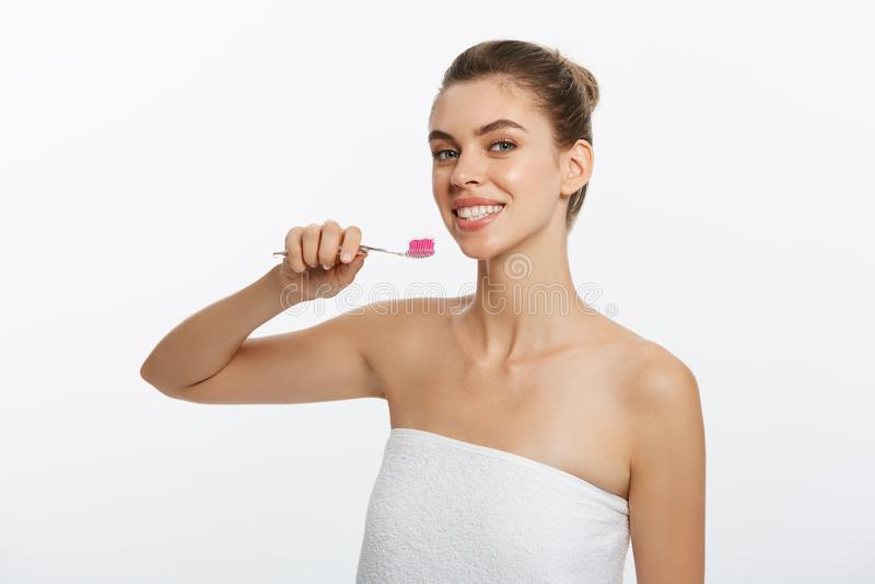 刷她的有牙刷的牙和看照相机的一名愉快的美丽的半赤裸妇女的秀丽画象 免版税库存图片