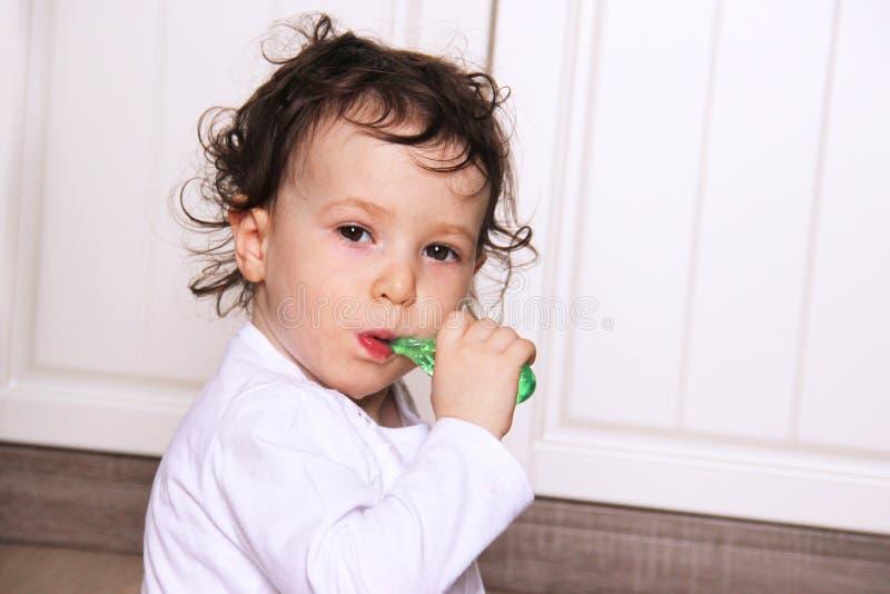 刷她的牙的严肃的矮小的女婴 两岁儿童 复制空间 图库摄影