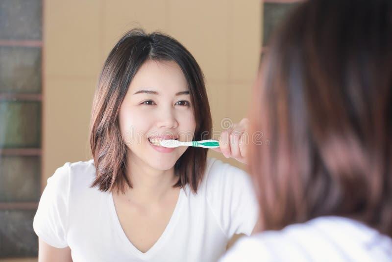 刷她的牙的少妇在镜子 在唤醒以后 库存图片