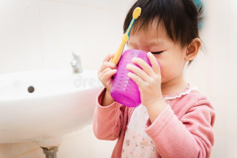 刷她的牙的甜亚裔儿童女孩 免版税库存图片