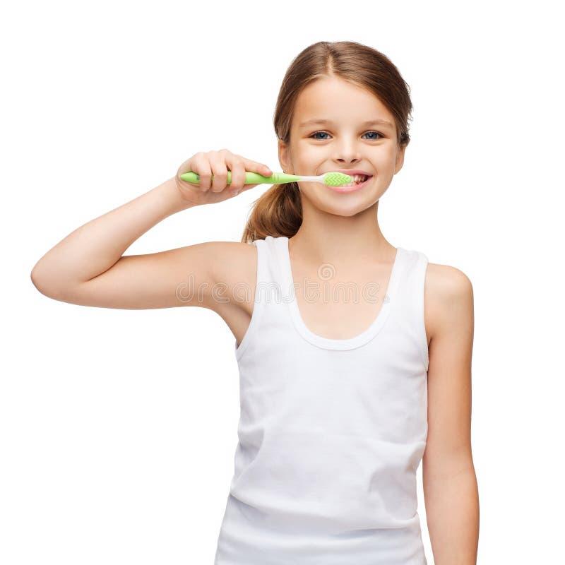 刷她的牙的空白的白色衬衣的女孩 图库摄影