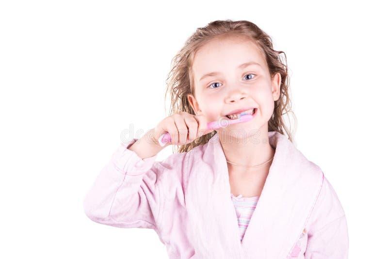 刷她的牙的美丽的愉快的微笑的小女孩在浴,阵雨以后 免版税库存图片