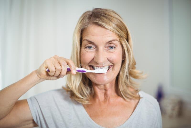 刷她的牙的资深妇女画象在卫生间里 免版税图库摄影