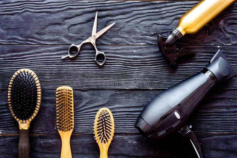 刷子、hairdryer和喷发剂在灰色木背景顶视图 免版税库存图片