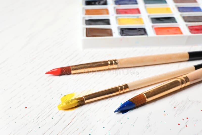 刷子和塑料调色板有五颜六色的油漆的 免版税库存照片