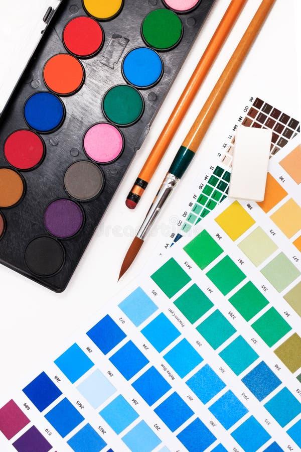 刷子,水彩教室组装、橡皮擦和摘要色板显示指南 库存照片