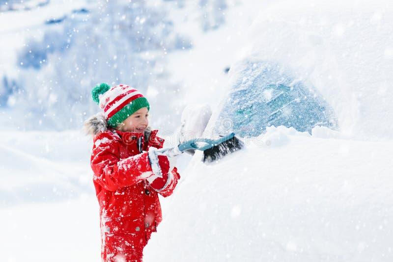 刷掉汽车的孩子 与冬天雪刷子的孩子 免版税图库摄影