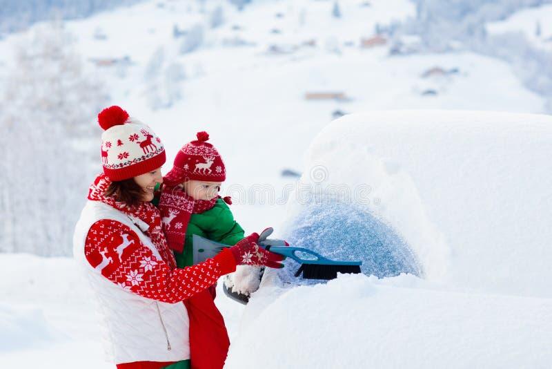 刷掉汽车的母亲和孩子在冬天 免版税库存图片