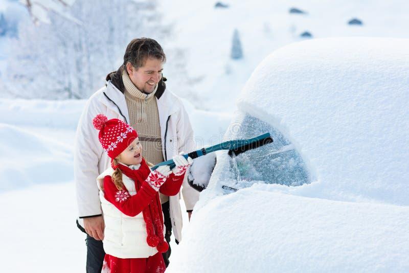 刷掉汽车的父亲和孩子在冬天 免版税图库摄影
