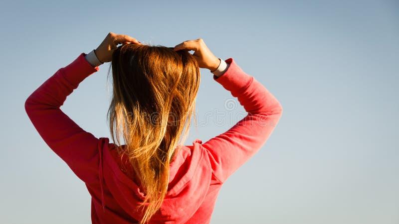 刷新她的发型的妇女梳室外的头发 免版税库存图片