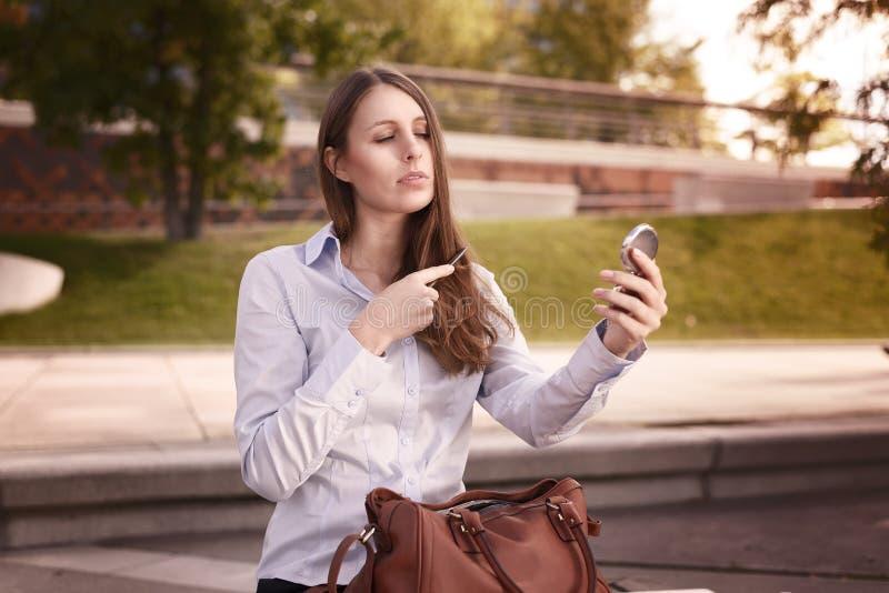 刷新她的在街道的少妇头发 免版税库存图片