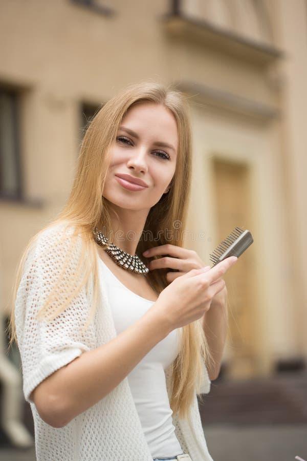 刷新她的在都市街道的妇女发型 免版税库存照片