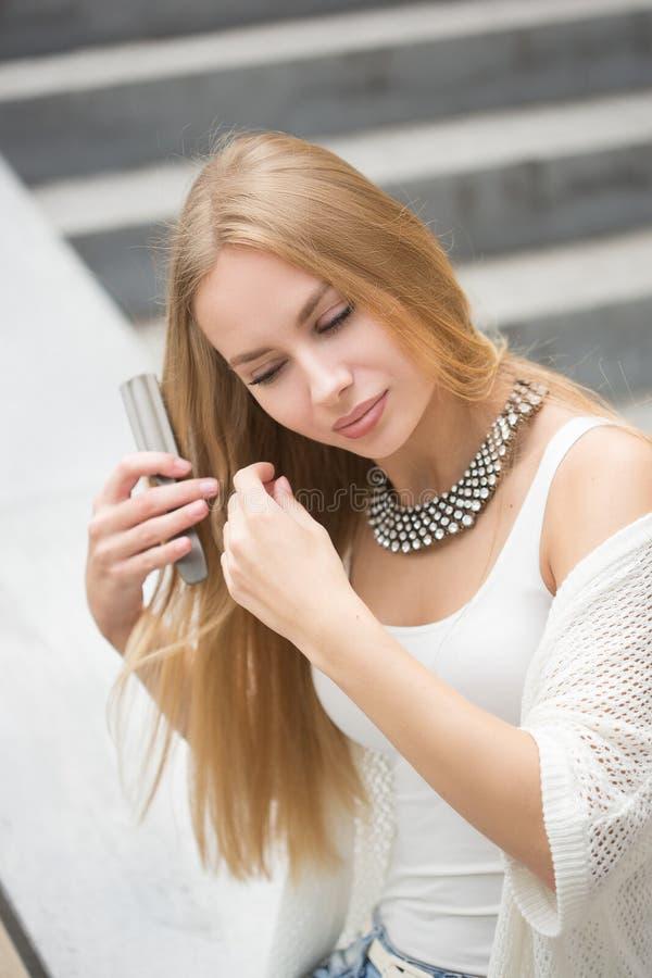 刷新她的在都市街道的妇女发型 图库摄影
