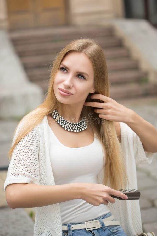 刷新她的在都市街道的妇女发型 免版税图库摄影