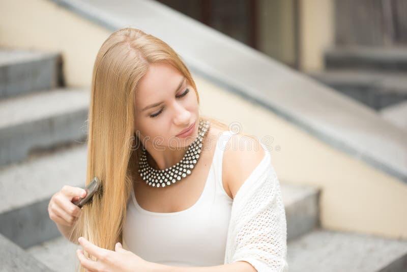 刷新她的在都市街道的妇女发型 免版税库存图片