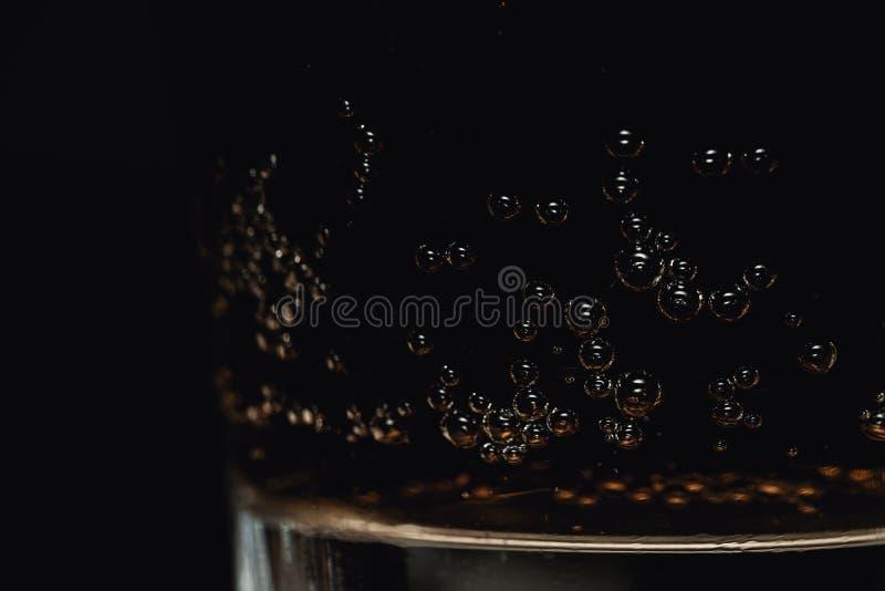 刷新的杯特写镜头与详细的泡影的可乐泡沫腾涌的饮料在黑暗的背景 免版税库存照片