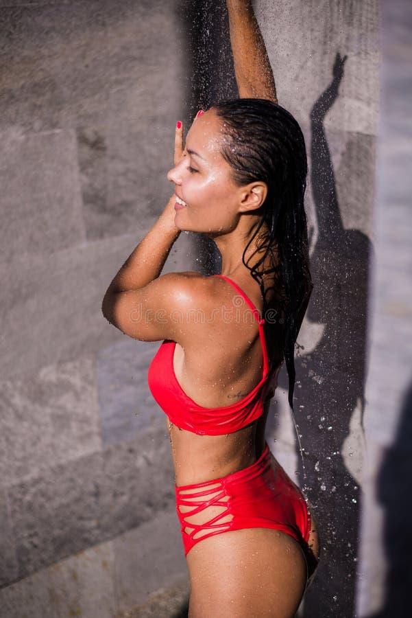 洗刷新的澡的红色泳装的运动的年轻美丽的性感的妇女在游泳在室外水池以后 室外 免版税库存图片