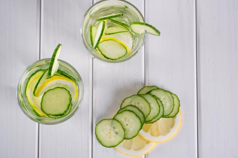 刷新的黄瓜鸡尾酒,柠檬水,在一块玻璃的戒毒所水在白色背景 玻璃水瓶柑橘饮料冰橙色夏天水 库存图片