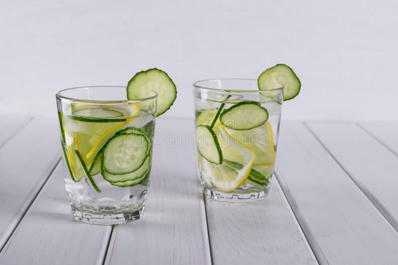 刷新的黄瓜鸡尾酒,柠檬水,在玻璃的戒毒所水 玻璃水瓶柑橘饮料冰橙色夏天水 免版税库存照片