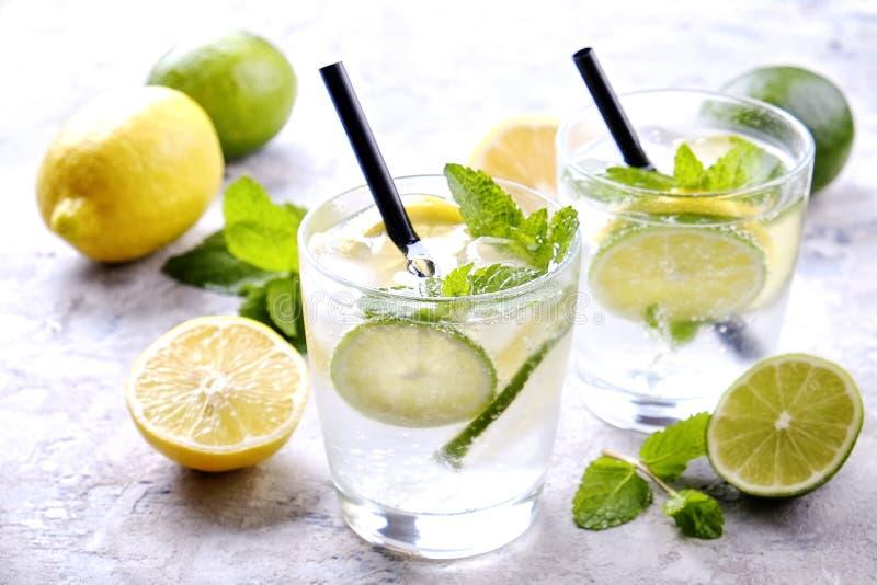 刷新非酒精mojito柠檬水饮料两块玻璃用有机柠檬,石灰切片,薄荷叶,秸杆,在gr的冰块 免版税库存照片
