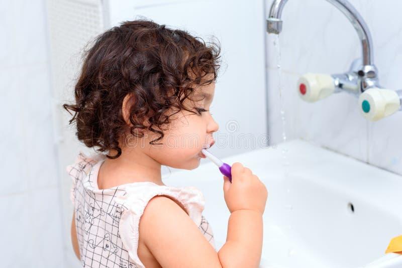刷牙的卷曲小小孩 孩子健康概念 儿童的牙齿卫生学 免版税图库摄影