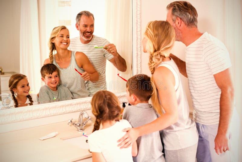 刷牙的父母和孩子在卫生间里 免版税库存照片