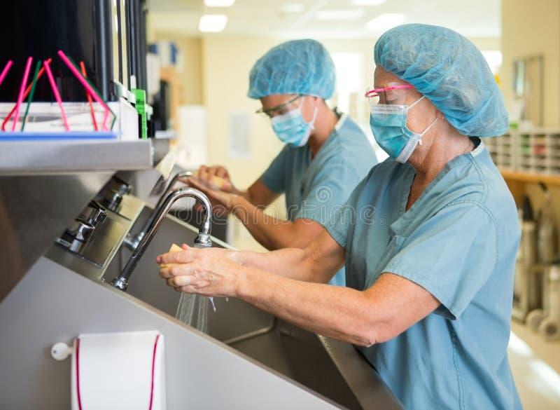 洗刷的手和胳膊在手术前 免版税库存照片
