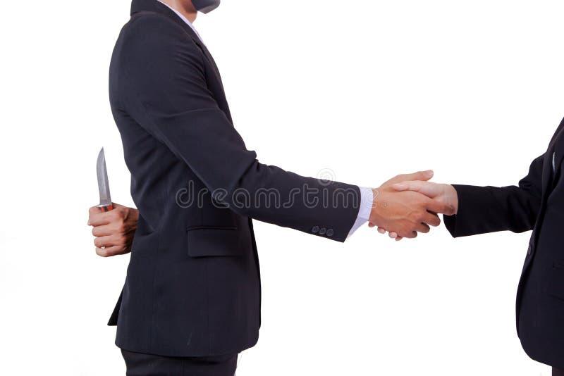 刺中,做成交,但是掩藏刀子的两个商人 库存照片