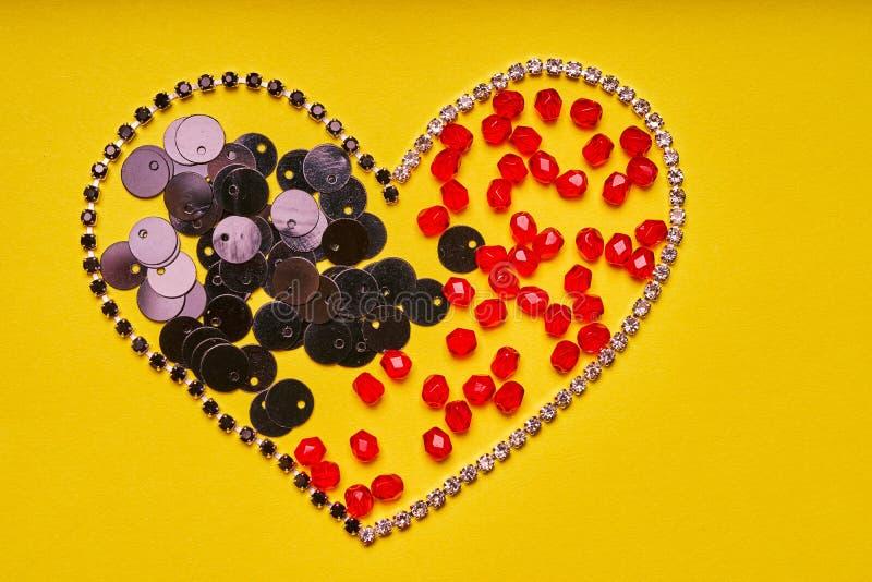 刺绣产品和工具 心脏、假钻石、衣服饰物之小金属片和红色roundels在黄色背景 免版税库存照片