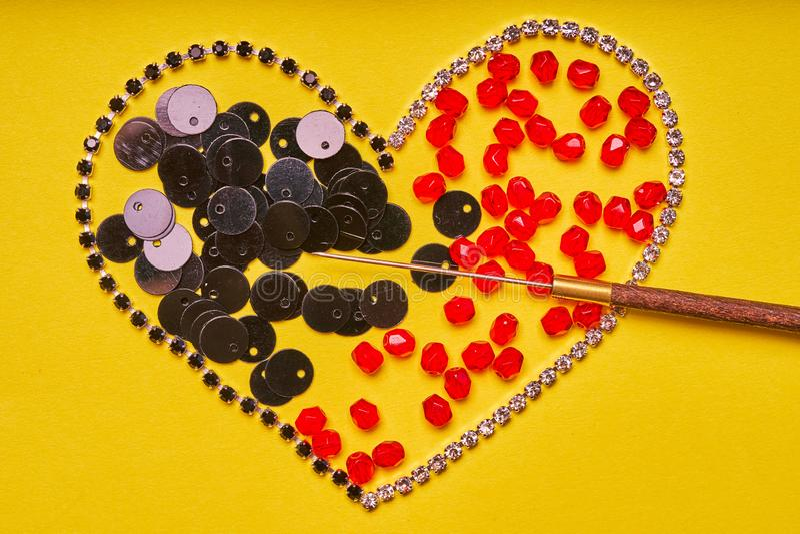 刺绣产品和工具 心脏、假钻石、衣服饰物之小金属片和红色roundels在黄色背景 免版税图库摄影