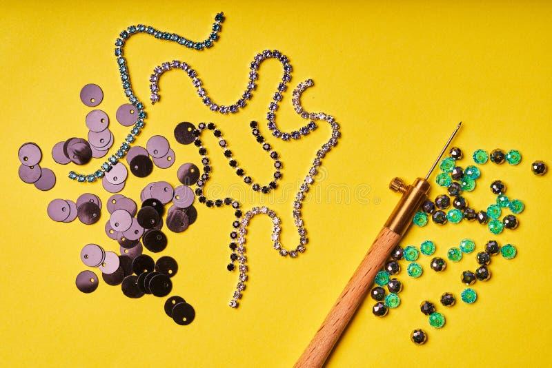 刺绣产品和工具 黑衣服饰物之小金属片、假钻石和吕内维尔勾子在黄色背景 免版税库存照片