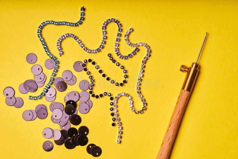 刺绣产品和工具 黑衣服饰物之小金属片、假钻石和吕内维尔勾子在黄色背景 免版税图库摄影