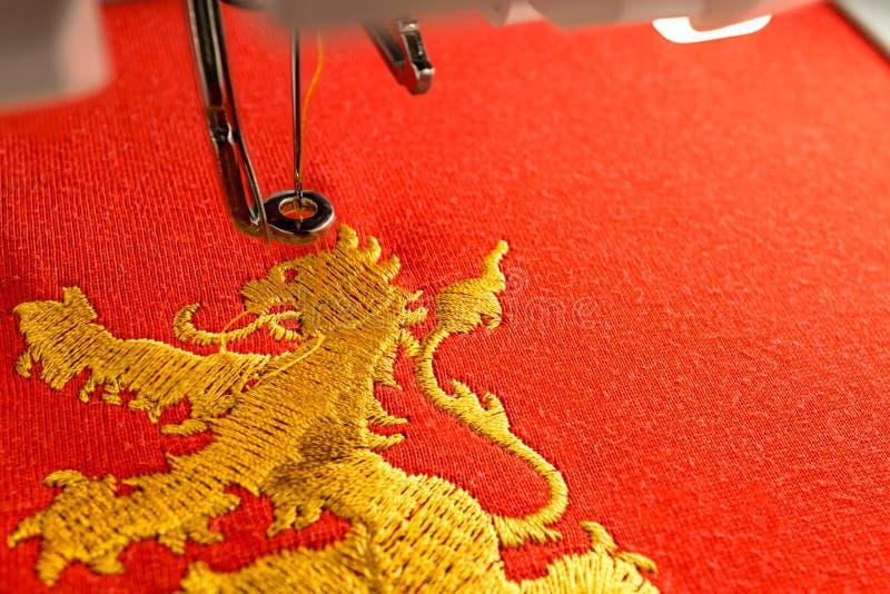 刺绣机器工作区和金狮子在红色织品设计 免版税图库摄影