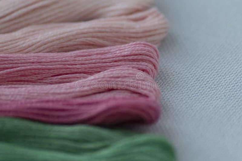 刺绣的多彩多姿的螺纹在轻的帆布 E 免版税库存照片