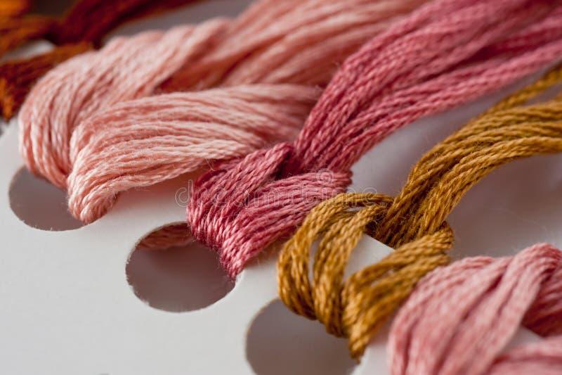 刺绣绣花丝绒的螺纹在纸基本的特写镜头射击 免版税库存图片