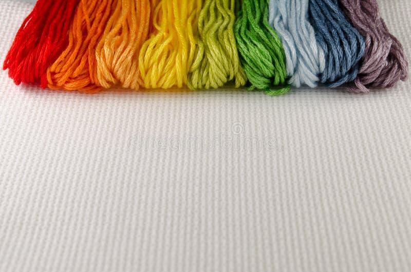刺绣的五颜六色的棉花螺纹在帆布 免版税库存图片