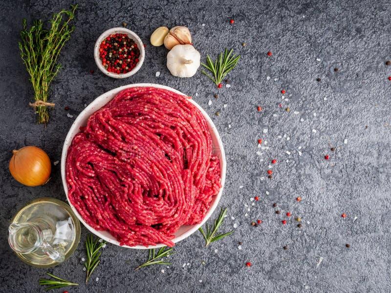 剁碎牛肉,与成份的绞肉烹调的在黑暗的gra 免版税库存图片