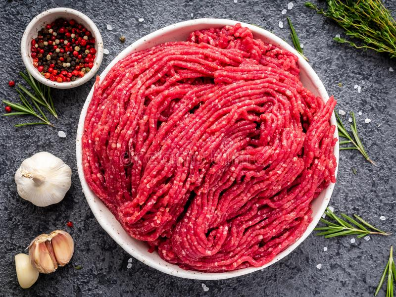 剁碎牛肉,与成份的绞肉烹调的在黑暗的gra 库存照片