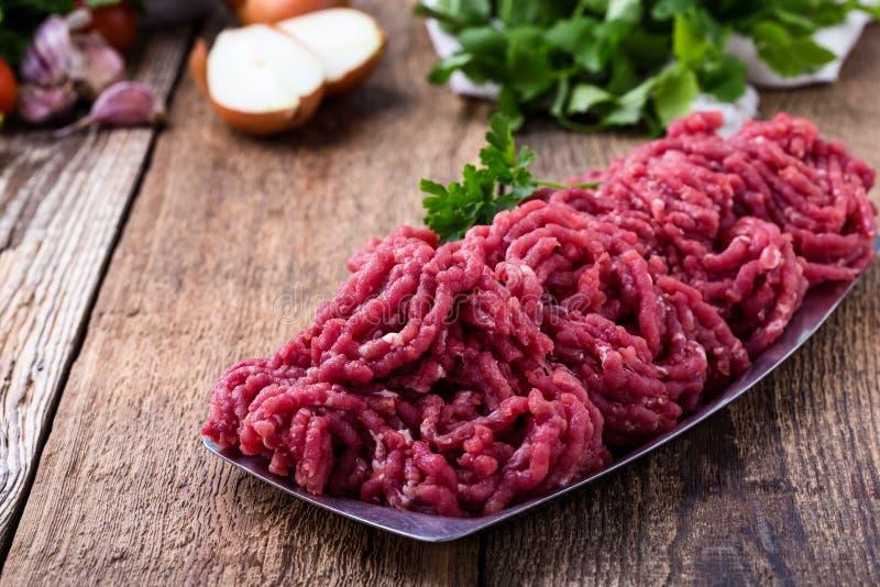 剁碎的牛肉,与烹调成份的未加工的绞肉 库存照片