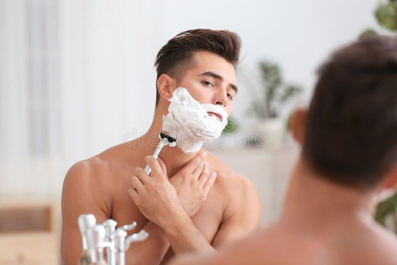 剃在镜子附近的年轻人 免版税库存照片