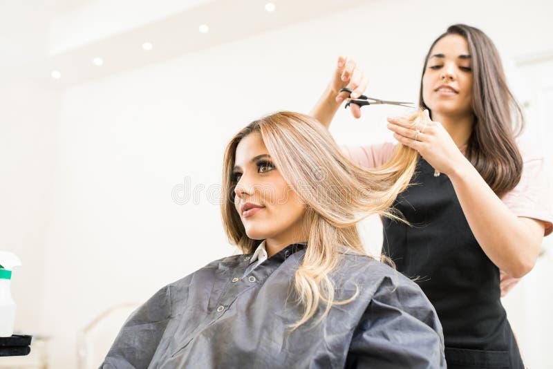 削减一些头发技巧的美发师 库存照片