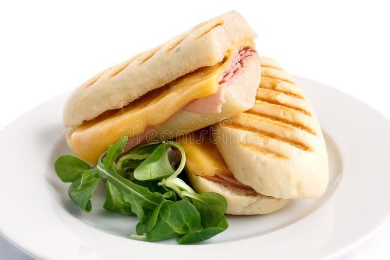 削减乳酪和火腿敬酒的panini融解 在有garn的白色板材上 免版税图库摄影