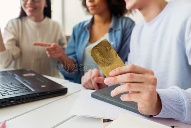 削减在他的手上拿着一张信用卡的观点的人,当他一起时看有女孩的膝上型计算机 图库摄影