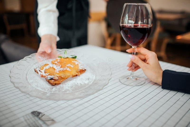 削减妇女的手有蛋糕的藏品板材看法  顾客的手有杯红酒 人们是里面在餐馆 图库摄影