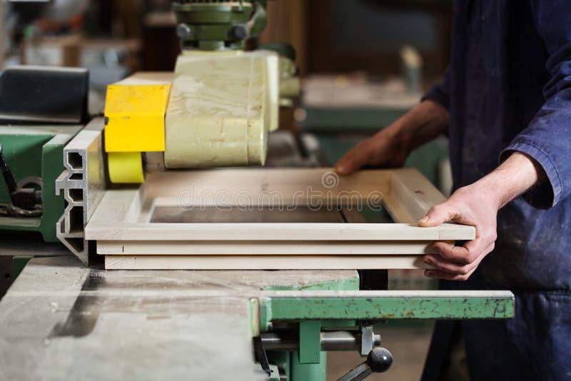 削减木窗架的木匠的手 免版税库存图片