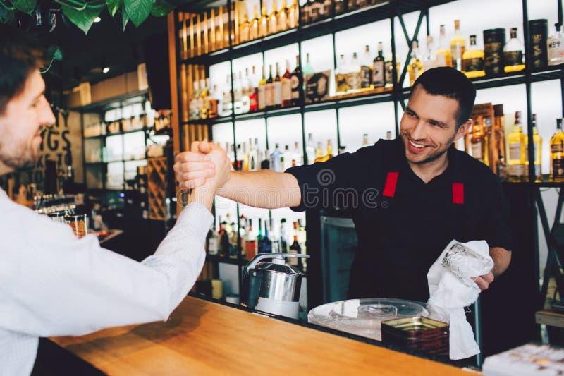 削减的男服务员招呼他的朋友和握他的手的观点 他是愉快看他的朋友 一切在a位于 免版税库存图片