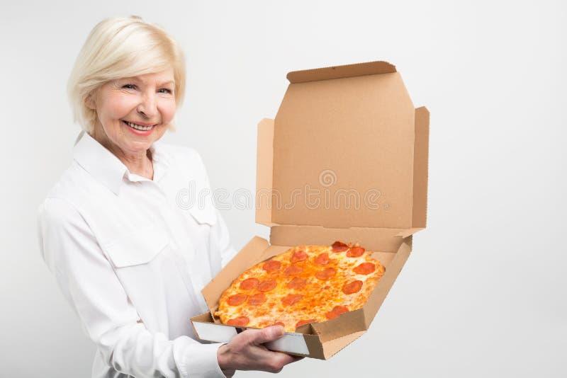 削减的祖母拿着大箱鲜美薄饼的观点 她喜欢它为人不是健康的速食despice 夫人 图库摄影