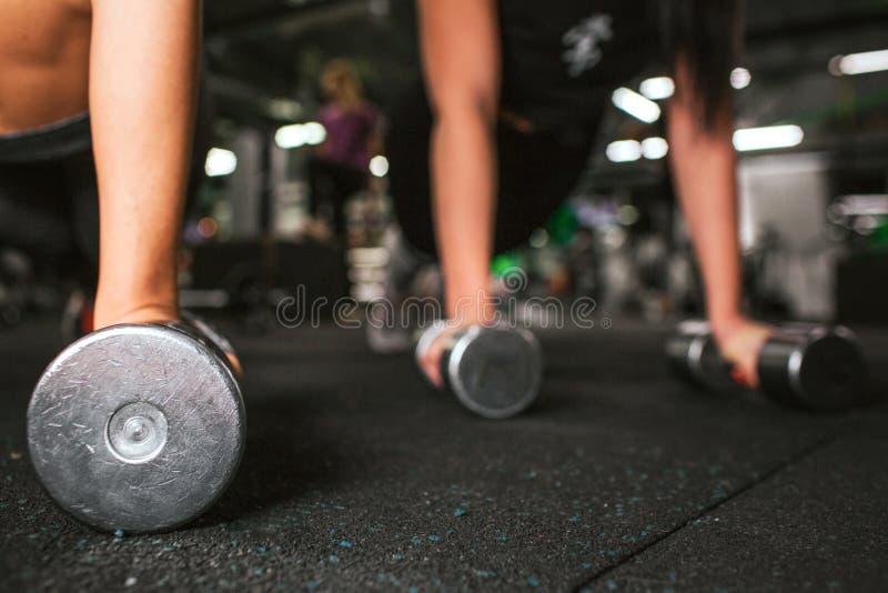 削减站立在哑铃的两只对年轻女人的手看法  他们在健身房的同样地板上  库存照片