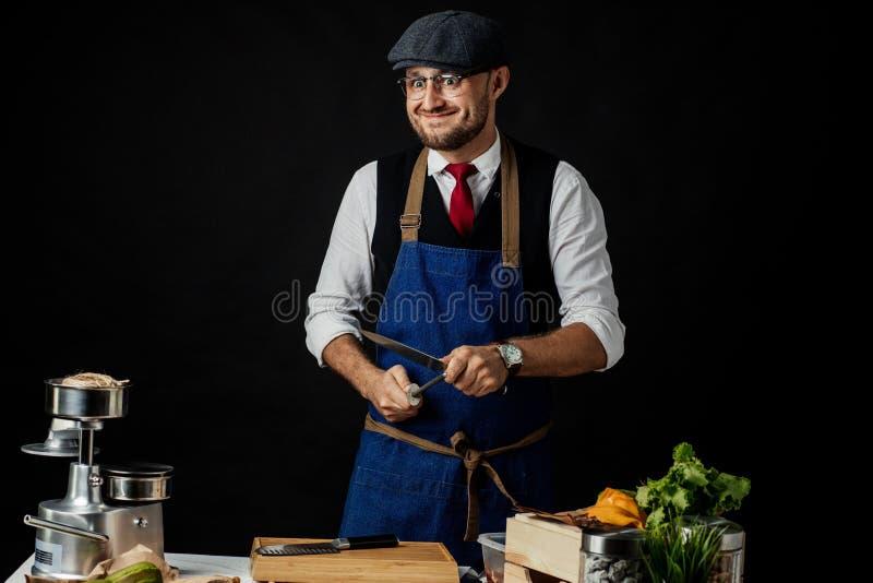 削尖刀子的男性厨师的中央部位在商业厨房里 免版税库存图片