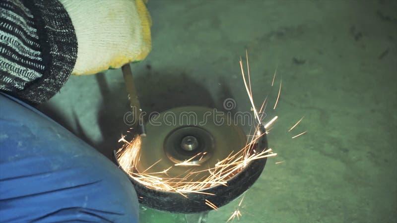 削尖和切开金属的指南由磨床 夹子 削尖在一个砂轮的金属 免版税库存图片